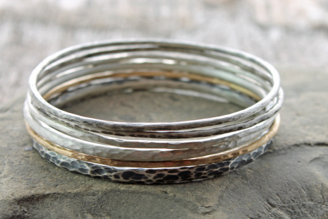 a beautiful stack of hammered bangles in sterling silver and 14k gold